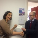Tom Hughes hands over a cheque from the proceeds of Carol Wagon 2015 to a member of Refugee Action Kingston